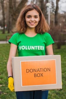 Weiblicher freiwilliger, der kasten für spenden hält