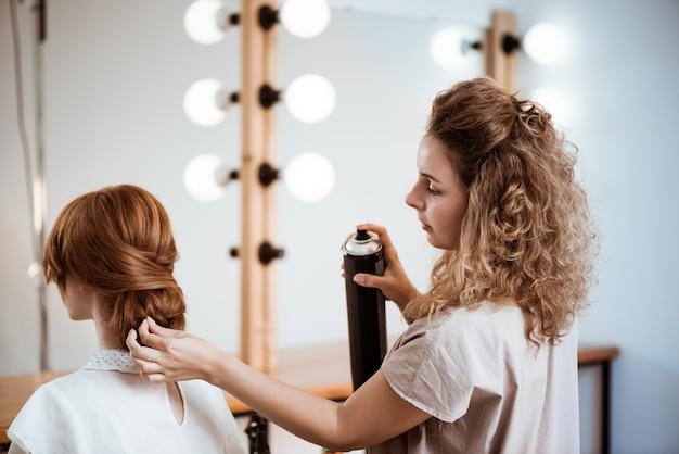 Weiblicher friseur, der frisur zu rothaariger frau im schönheitssalon macht