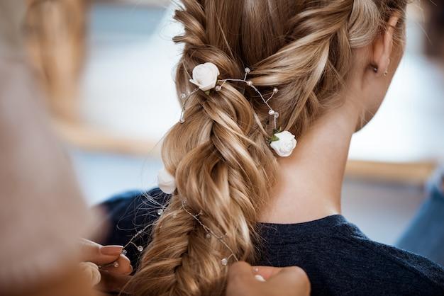 Weiblicher friseur, der frisur zur blonden frau im schönheitssalon macht