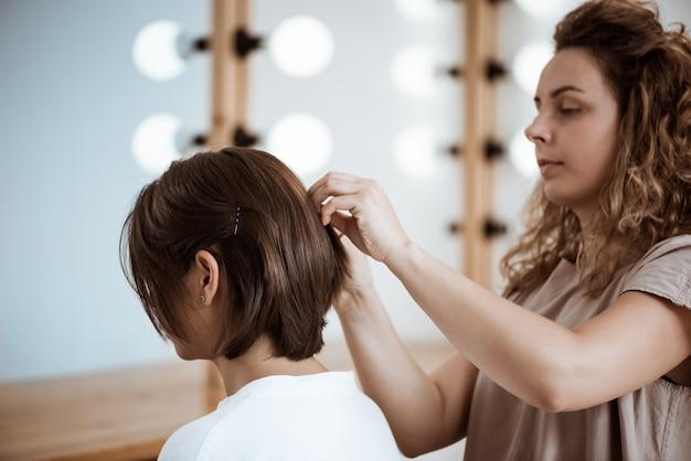 Weiblicher friseur, der frisur zur brünetten frau im schönheitssalon macht