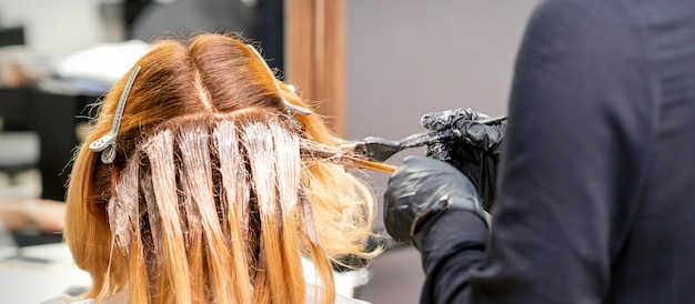 Weiblicher friseur, der haare der jungen kaukasischen frau im friseursalon färbt