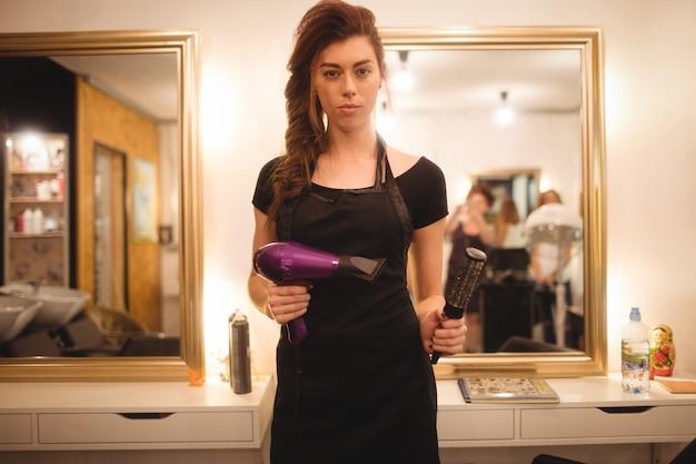 Weiblicher friseur, der haartrocknermaschine und -haarbürste hält