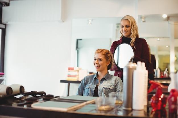 Weiblicher friseur, der kundenhaar stylt
