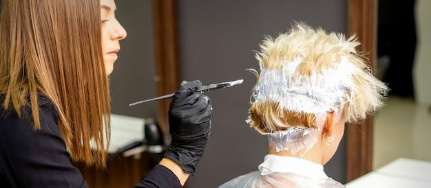 Weiblicher friseur, der kurzes blondes haar einer jungen frau in einem friseursalon färbt