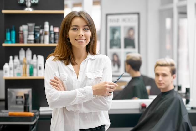 Weiblicher friseur, der vor jungem männlichem kunden aufwirft.