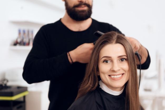 Weiblicher friseur richten braunes haar zur hübschen frau gerade.