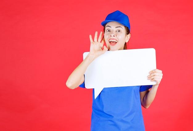 Weiblicher führer in blauer uniform, der eine weiße rechteckige infotafel hält und ohren öffnet und schreit.