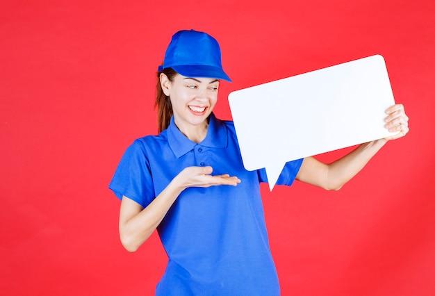 Weiblicher führer in blauer uniform, der eine weiße rechteckige infotafel hält.