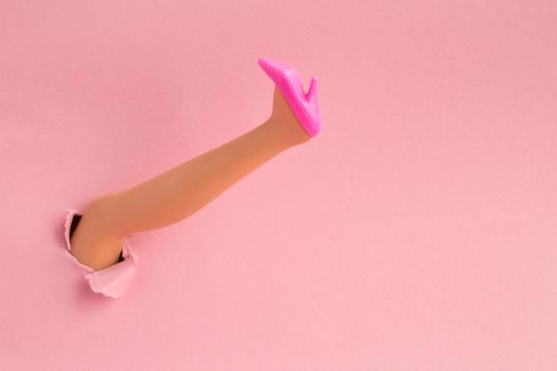 Weiblicher fuß in rosa schuh durch ein loch zerrissenes papier eingeführt. speicherplatz kopieren. nahansicht.