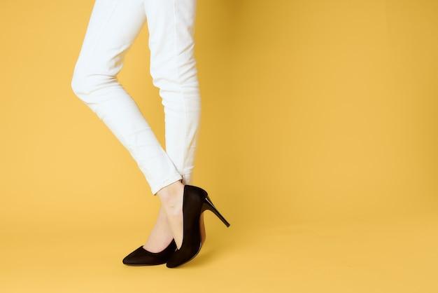 Weiblicher fuß schwarzer schuhmodebekleidungsstudio gelber hintergrund