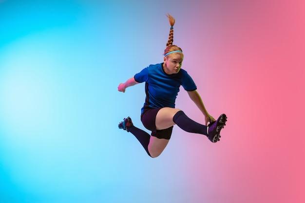 Weiblicher fußball, fußballspielertraining in aktion lokalisiert auf gradientenstudiohintergrund im neonlicht