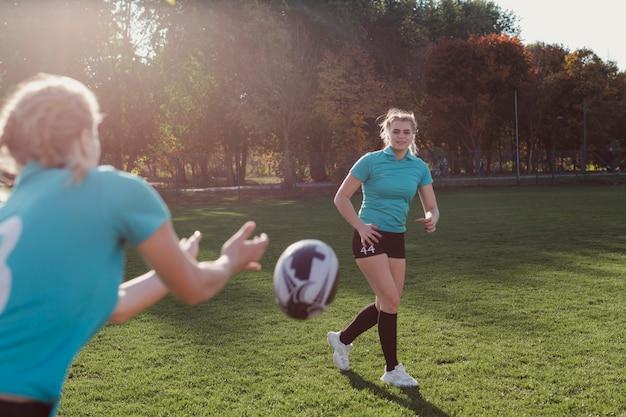 Weiblicher fußballspieler, der ball führt