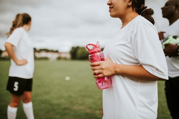 Weiblicher fußballspieler, der eine wasserflasche hält