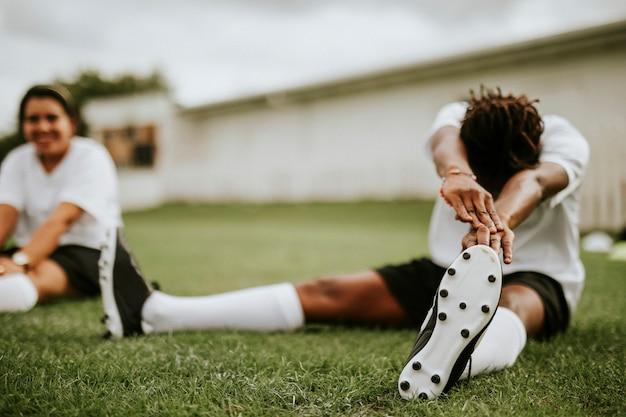 Weiblicher fußballspieler, der vor einem match ausdehnt