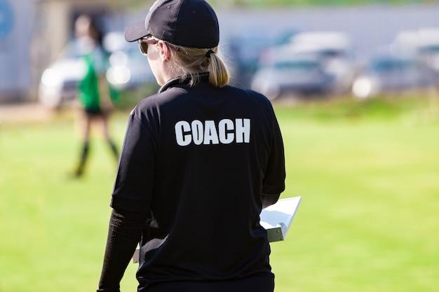 Weiblicher fußballtrainer im schwarzen trainer-hemd an einem sportplatz im freien, der ihr teamplay aufpasst