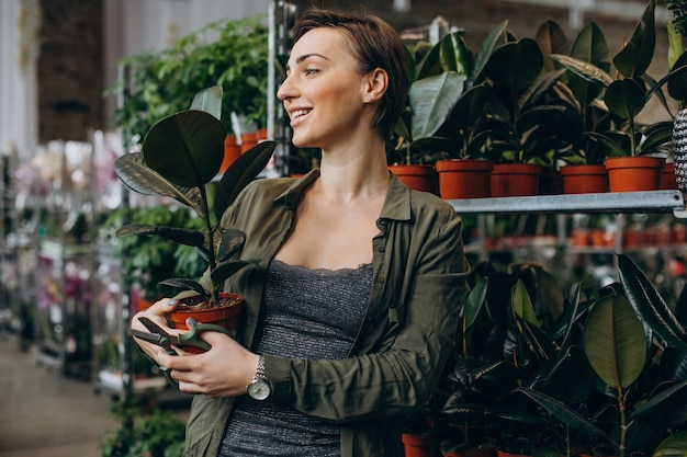Weiblicher gärtner am pflanzenhaus mit pflanzen und blumen