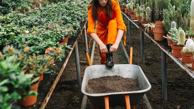 Weiblicher gärtner, der gummistiefel im gewächshaus bindet