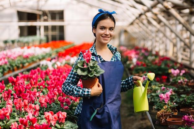 Weiblicher gärtner, der im gewächshaus arbeitet