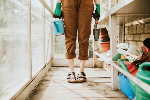Weiblicher gärtner, der vorbereitet, die blume in einem gewächshaus zu pflanzen