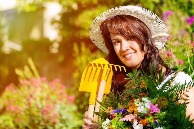Weiblicher gärtner mit blumen im sonnenbeschienen garten