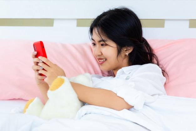 Weiblicher gebrauch smartphone des jugendlichen auf dem bett