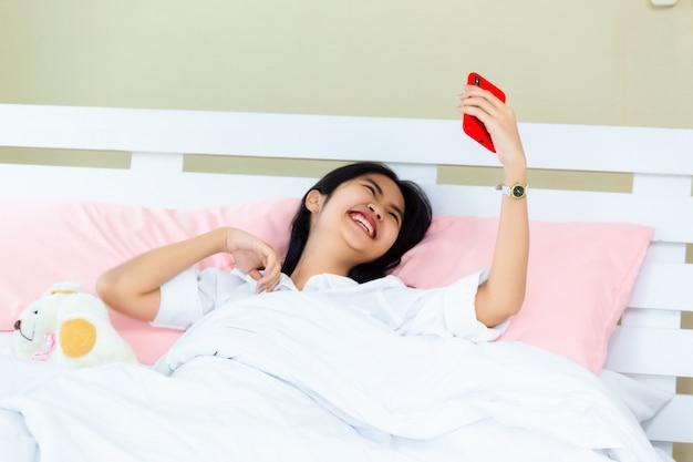 Weiblicher gebrauch smartphone des jugendlichen, der auf dem bett plaudert