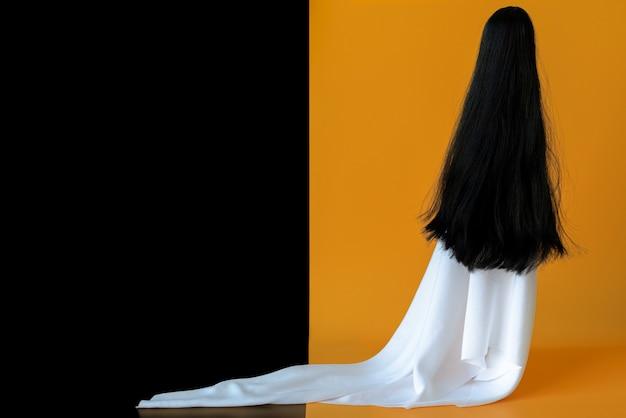 Weiblicher geist des langen haares mit weißem blattkostüm mit schwarzem und orange hintergrund. minimales halloween unheimlich.