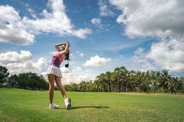 Weiblicher golfspieler, der golf im professionellen golfplatz spielt