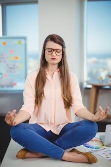 Weiblicher grafikdesigner, der auf tisch sitzt und meditiert