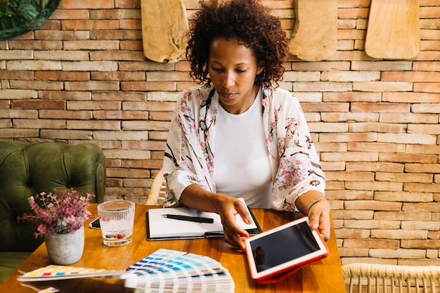 Weiblicher grafikdesigner, der die farbmuster in der hand halten digitale tablette betrachtet