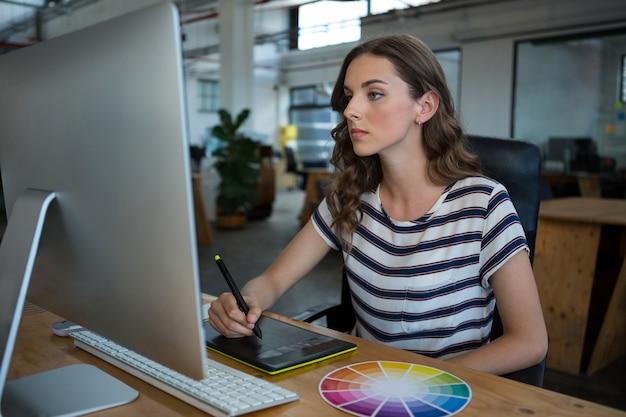 Weiblicher grafikdesigner, der grafiktablett am schreibtisch verwendet