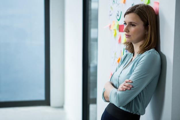 Weiblicher grafikdesigner, der mit gekreuzten händen im kreativen büro steht