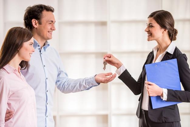Weiblicher grundstücksmakler gibt dem jungen paarschlüssel von der neuen wohnung.