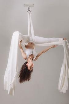 Weiblicher gymnast, der silk luftakrobatik tut