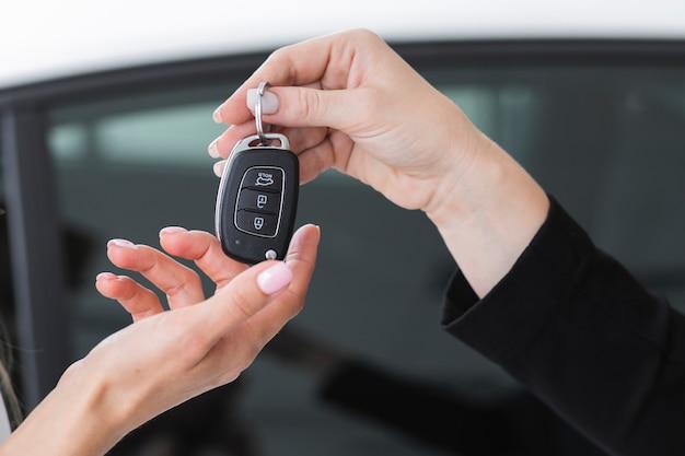 Weiblicher händler, der schlüssel zu einem auto anbietet