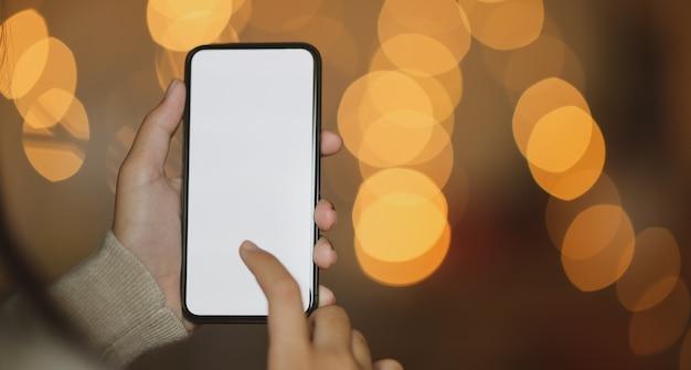 Weiblicher haltener smartphone in der magischen nachtzeit