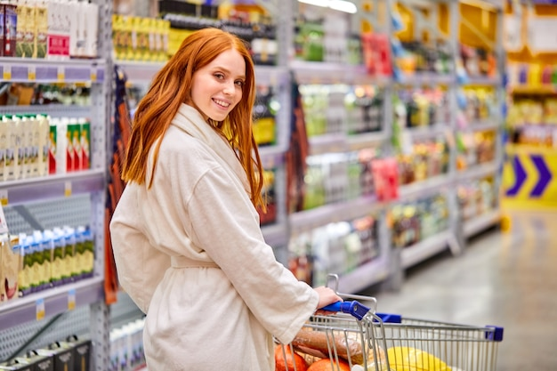 Weiblicher haltewagen im supermarkt, der durch regale mit lebensmitteln im lebensmittelgeschäft geht