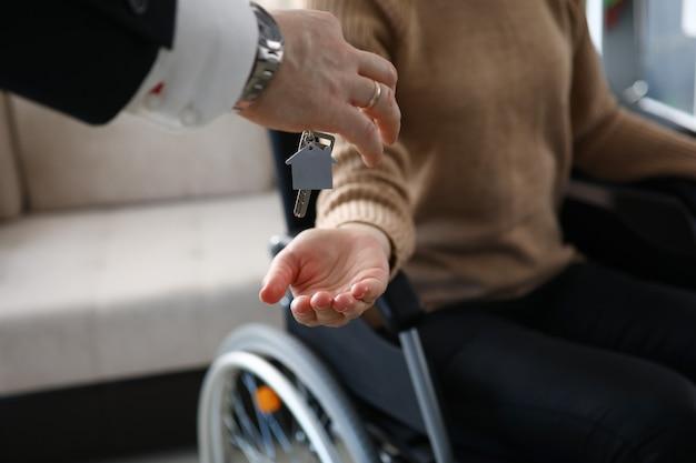 Weiblicher handgriff geben schlüssel mit schlüsselbund aus neuem haus und geben an behinderte.
