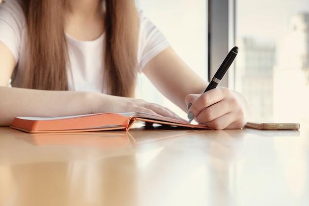 Weiblicher handstift zum schreiben eines tagebuchs