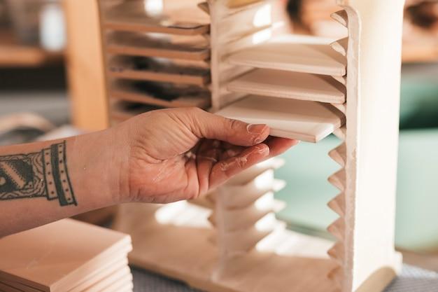 Weiblicher handwerker, der die gemalten weißen keramikfliesen im kleinen gestell vereinbart