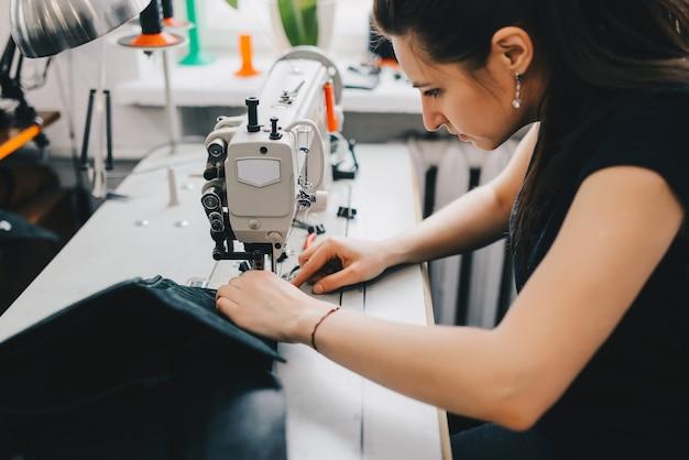 Weiblicher handwerker, der schwarzes leder auf nähmaschine verlegt