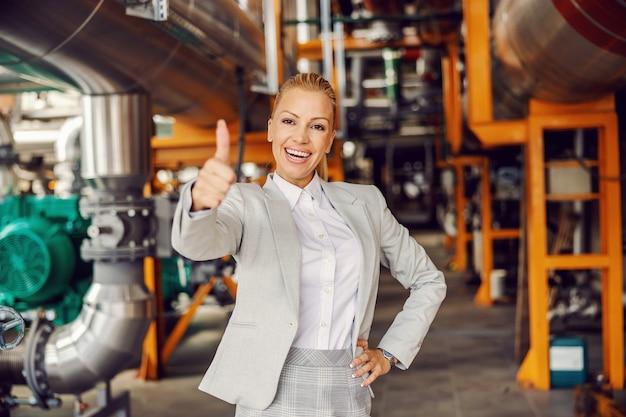 Weiblicher heizkraftwerkseigner im anzug, der in der einrichtung steht und daumen hoch zeigt.