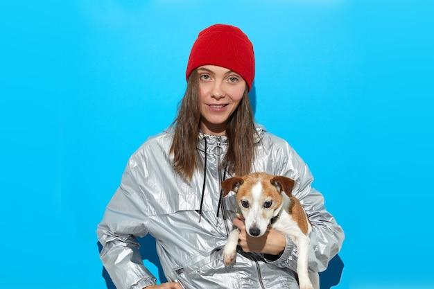 Weiblicher hipster im warmen outfit stehend mit niedlichem hund
