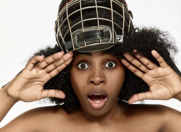 Weiblicher hockeyspieler schließen helm und maske über weißer wand. afroamerikanermodell