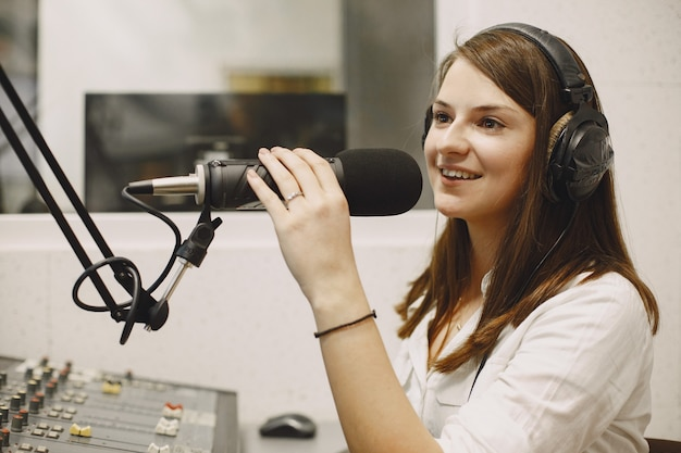 Weiblicher host, der über mikrofon kommuniziert. frau im radiostudio.