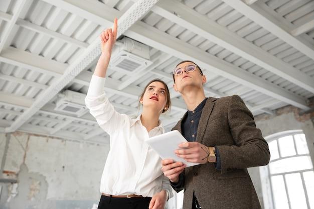 Weiblicher immobilienmakler, der einem jungen mann nach einer diskussion über hauspläne ein neues zuhause zeigt