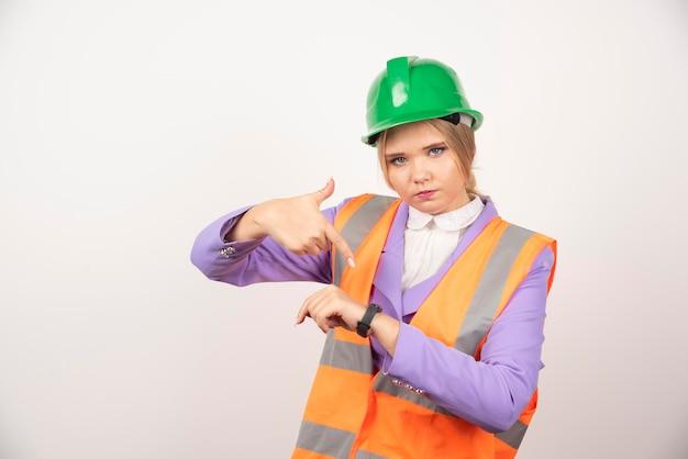 Weiblicher industriearbeiter, der zeit auf weißem hintergrund zeigt. hochwertiges foto