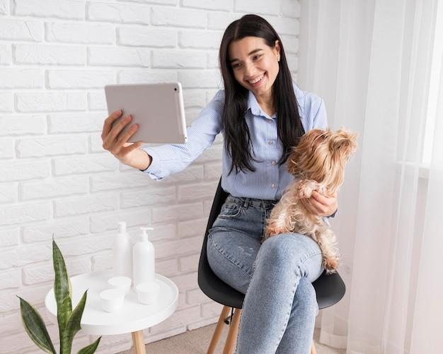 Weiblicher influencer zu hause mit tablette und hund
