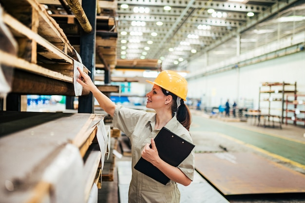 Weiblicher ingenieur, der an der schwerindustriefabrik arbeitet.