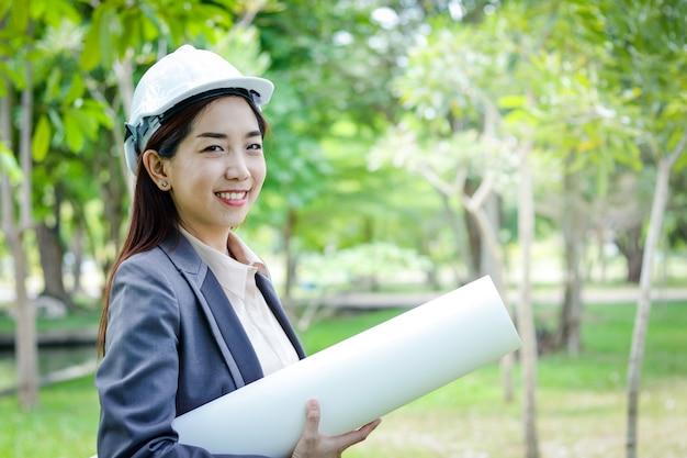 Weiblicher ingenieur, der einen weißen schutzhelm hält eine papierrolle trägt sie arbeitet mit der umwelt.